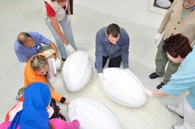 Varias personas tocando una obra de arte