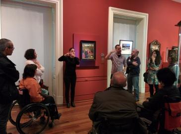 Un grupo de personas visitando el museo con un guía y un intérprete de LSE