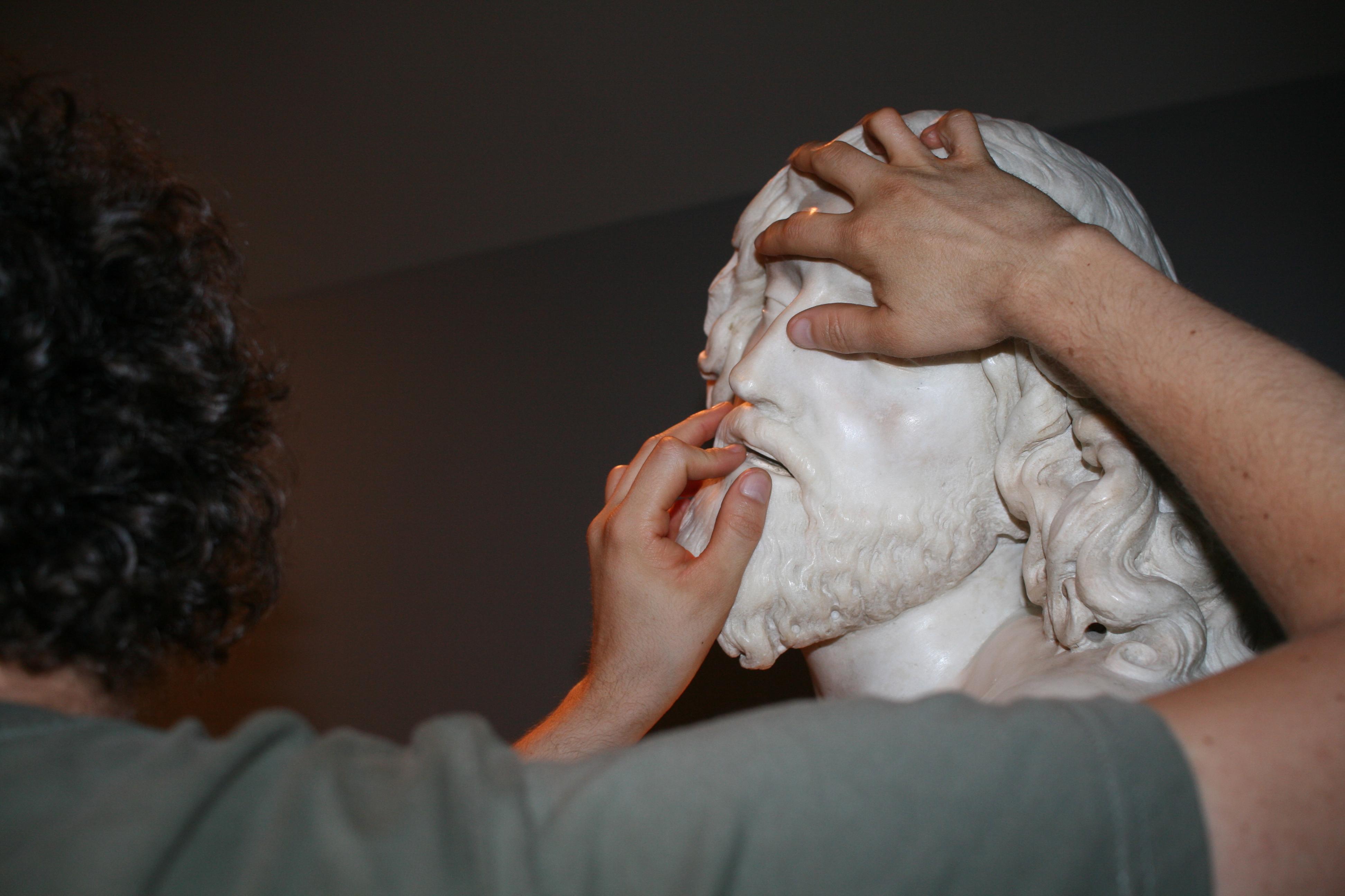 Educador ciego tocando escultura de mármol
