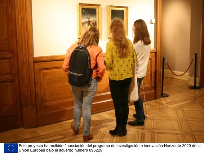 Tres personas observando las obras El aquelarre y Las Brujas de Goya.