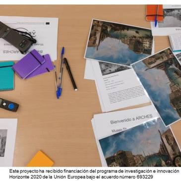 Sobre una mesa se ven reproducciones de una pintura de paisaje, papeles, bolis y grabadoras