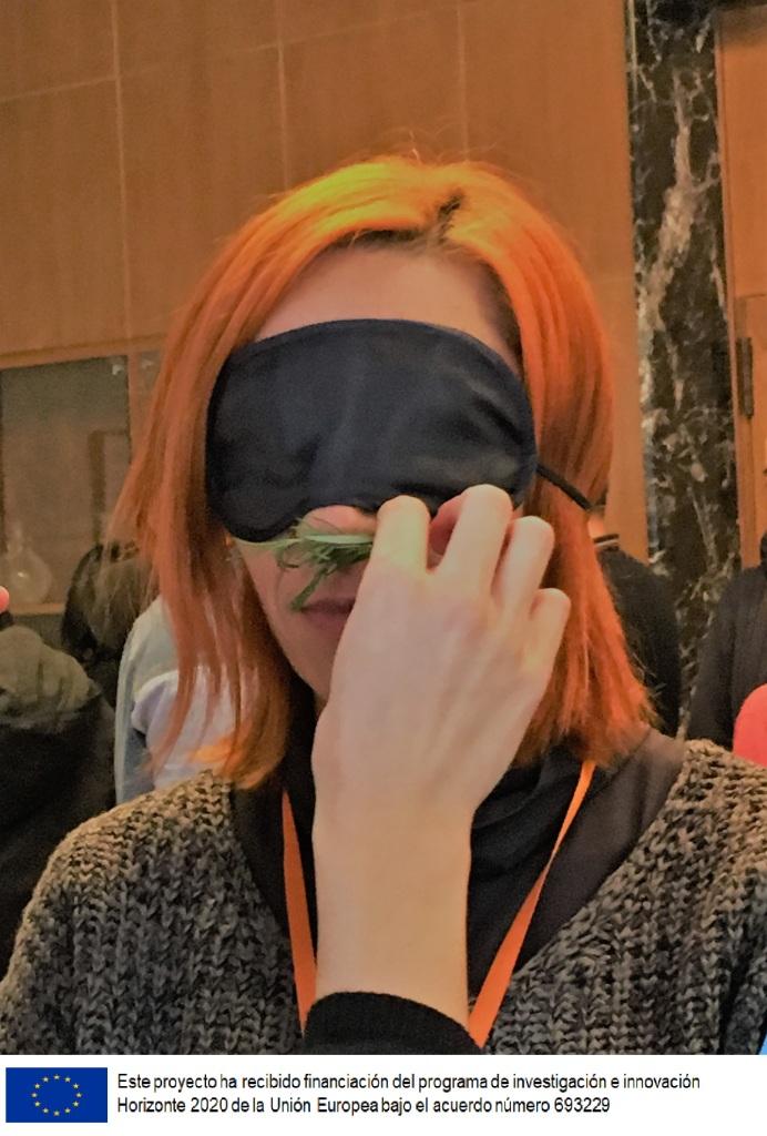 Una mujer con los ojos tapados por un antifaz, huele las hojas qeu le da a oler otra persona