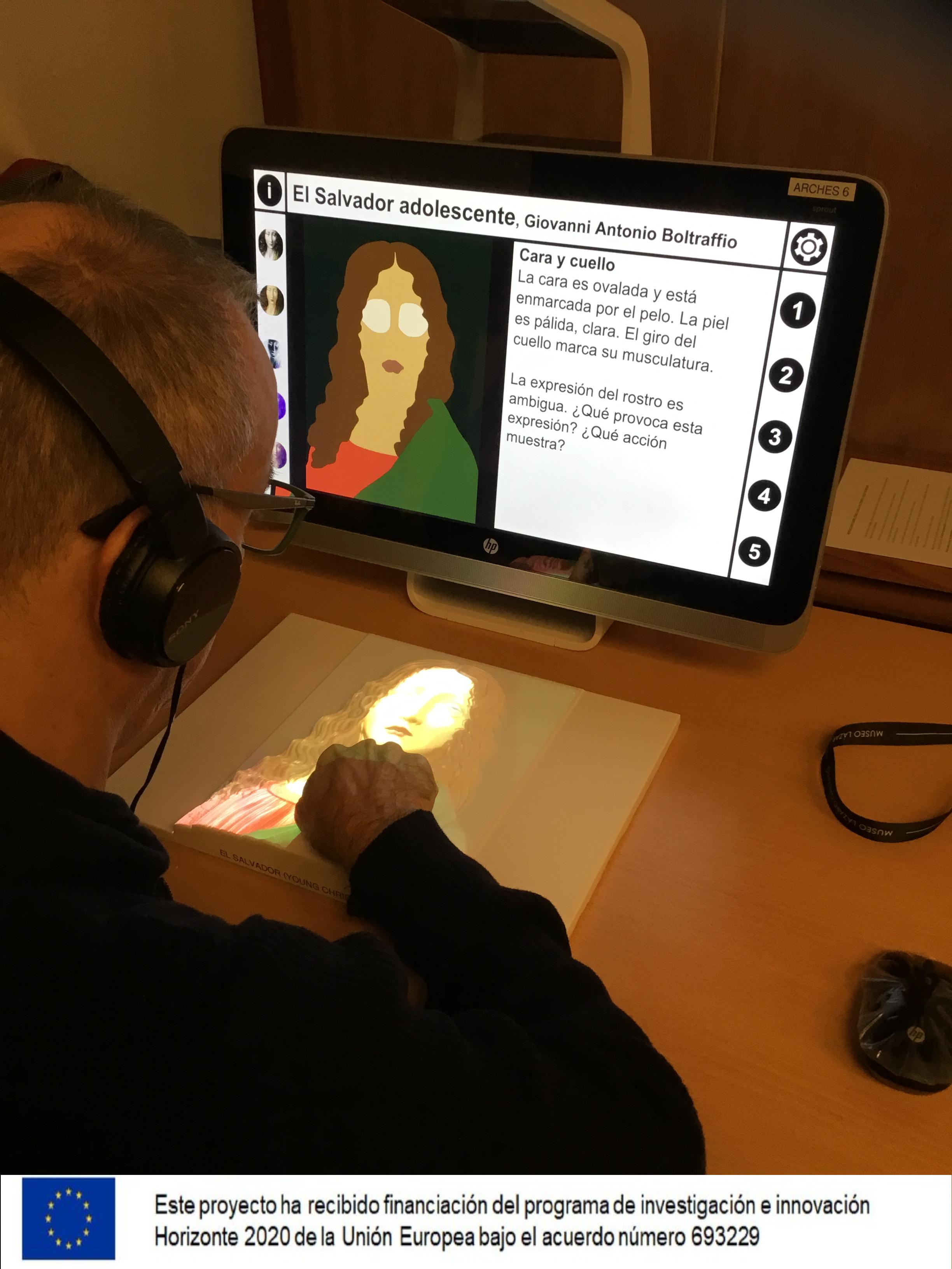 Participante tocando el relieve y escuchando el contenido táctil