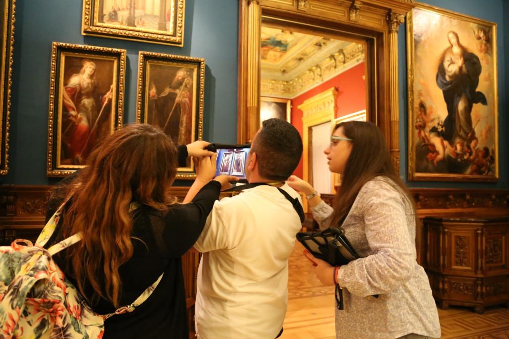 Tres participantes del grupo ARCHES Madrid probando una tableta frente a una obra del Museo Lázaro Galdiano
